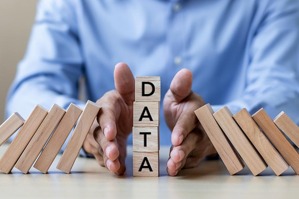 Man with hands between domino blocks that are cascading into a set of four stacked blocks with the letters DATA printed on them.