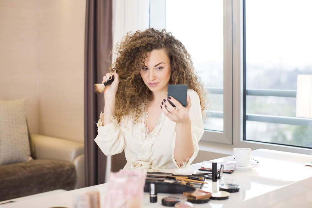 Shutterstock_560720707 Young woman putting some makeup